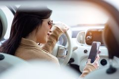 Beautiful young woman using her mobile phone in the car. royalty free stock images