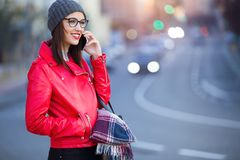 Beautiful young woman using her mobile phone in the city. Stock Images