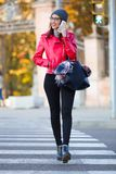 Beautiful young woman using her mobile phone in the city. Royalty Free Stock Images