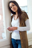 Beautiful young woman using her mobile phone at home. Royalty Free Stock Photography