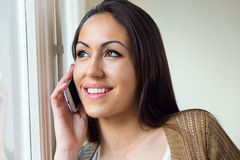 Beautiful young woman using her mobile phone at home. Stock Photography