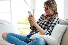 Beautiful young woman using her mobile phone at home. Stock Image