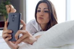 Beautiful young woman using her mobile phone at home. Stock Photo