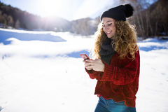 Beautiful young woman using her mobile phone over winter backgro Royalty Free Stock Photo