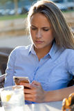 Beautiful young woman using her mobile phone in a restaurant ter Royalty Free Stock Photos