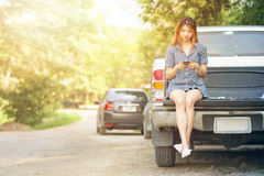 Beautiful young woman using her mobile phone sit on car Stock Images