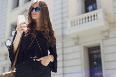 Beautiful young woman using her mobile phone in the street. Royalty Free Stock Photography