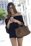 Beautiful young woman using her mobile phone in the street. Royalty Free Stock Photos