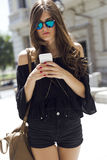 Beautiful young woman using her mobile phone in the street. Stock Image