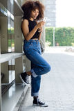 Beautiful young woman using her mobile phone in the street. Royalty Free Stock Image