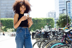 Beautiful young woman using her mobile phone in the street. Royalty Free Stock Images