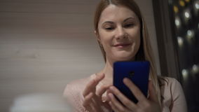 Beautiful young woman using her smartphone in a cafe. Browsing internet, communicating with friends. Beautiful attractive young woman using her cellphone in a stock video footage