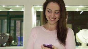 Woman uses her smartphone at the jewerly shop. Beautiful young woman using her smartphone at the jewerly shop. Close up of pretty caucasian lady holding Royalty Free Stock Image