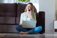 Beautiful young woman using her smartphone while working with laptop at home. Portrait of beautiful young woman using her smartphone while working with laptop Stock Image