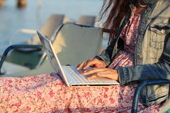 Beautiful young woman using laptop at beach. Beautiful young woman using white laptop at beach Stock Photo