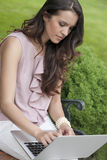 Beautiful young woman using laptop on bench in park Royalty Free Stock Photography