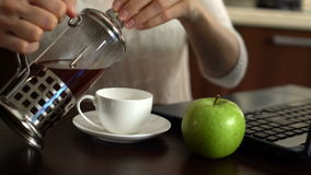 Beautiful young woman using laptop at home in the kitchen. Pouring a cup of coffee. Apple on table. stock video footage