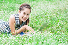 Beautiful young woman using laptop lying at meadow Royalty Free Stock Photos