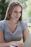 Beautiful young woman using laptop outdoors Stock Photos