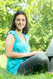 Beautiful young woman using laptop in the park Stock Photography