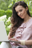 Beautiful young woman using laptop in park Stock Photography