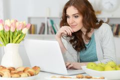 Woman  using  laptop  at table Stock Photos