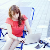 Beautiful young woman using laptop and typing outdoors Royalty Free Stock Photos