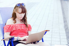 Beautiful young woman using laptop and typing outdoors Royalty Free Stock Photography