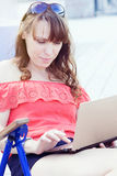 Beautiful young woman using laptop and typing outdoors Stock Images