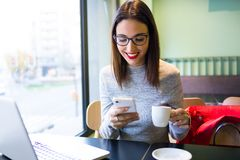 Beautiful young woman using mobile phone while drinking coffee in the cafe. Royalty Free Stock Images