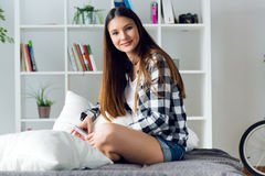 Beautiful young woman using mobile phone at home. Stock Photos