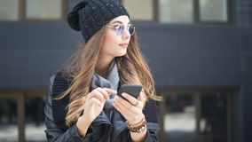 Beautiful young woman using mobile phone in outdoors Stock Images