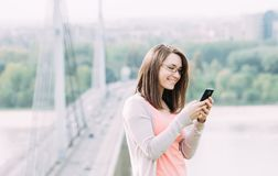 Young woman using mobile phone outdoors in a city. Beautiful young woman using mobile phone outdoors in a city Stock Photos