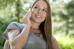Beautiful young woman using mobile phone in park Royalty Free Stock Images
