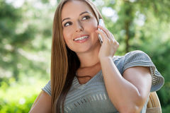 Beautiful young woman using mobile phone in park Stock Photography