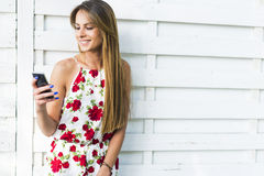 Beautiful young woman using phone while leaning against a white Royalty Free Stock Photo
