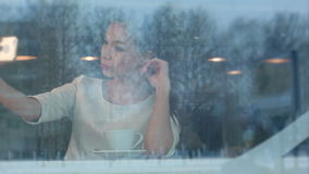 Beautiful young woman using phone to check her make up and take a selfie. In a cafe viewed through the window. Professional shot on BMCC RAW with high dynamic stock footage