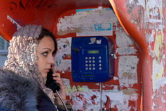 Beautiful young woman using a public payphone royalty free stock image