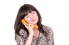 Beautiful young woman using retro orange telephone Royalty Free Stock Photos