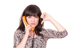 Beautiful young woman using retro orange telephone Royalty Free Stock Images