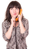 Beautiful young woman using retro orange telephone Royalty Free Stock Photo