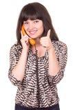 Beautiful young woman using retro orange telephone Stock Images