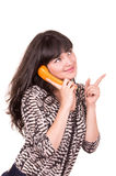 Beautiful young woman using retro orange telephone Stock Photo