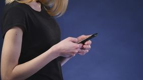 Beautiful young woman using smart phone with black background stock footage