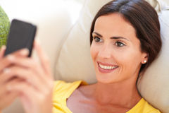 Beautiful young woman using a smart phone. Close up of a beautiful young woman using a smart phone while lying on her back Stock Photo
