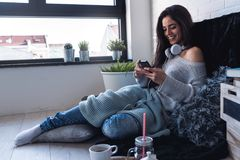 Beautiful young woman using smart phone at home in the morning. Beautiful young woman in cozy reading corner at home using smart phone Stock Image