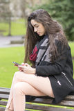 Beautiful young woman using smart phone in the park. Woman looking message in the smart phone, outdoor Royalty Free Stock Photos