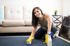 Cheerful woman cleaning carpet with help of blue brush and deter. Beautiful young woman using a spray and a brush while cleaning carpet in the house Stock Photography