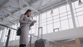 Beautiful young woman using tablet computer at airport. Elegant businesswoman in terminal with suitcase waiting plane stock footage