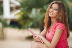 Beautiful young woman using tablet pc outdoor. Royalty Free Stock Photos